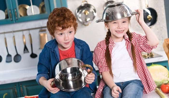 kids sitting in kitchen with pots and pans